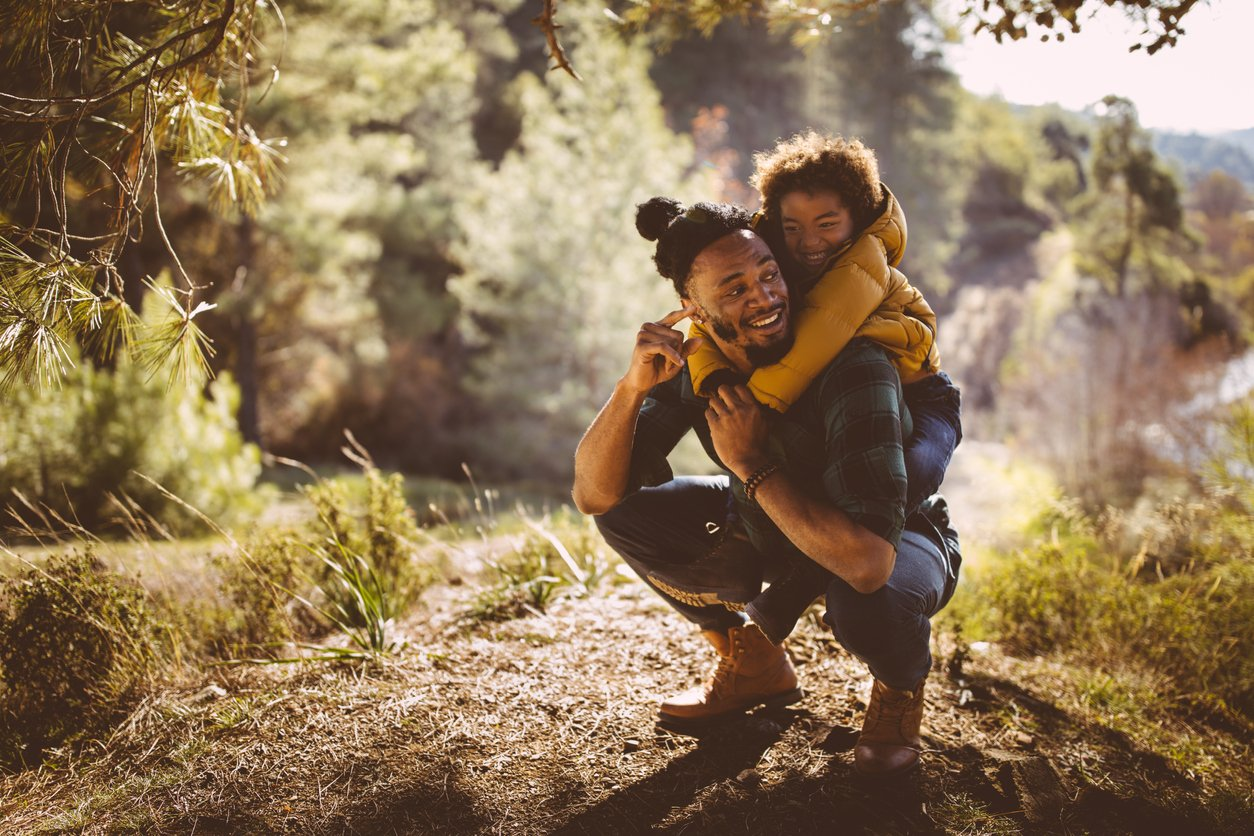 Father and son having fun with piggyback ride in forest