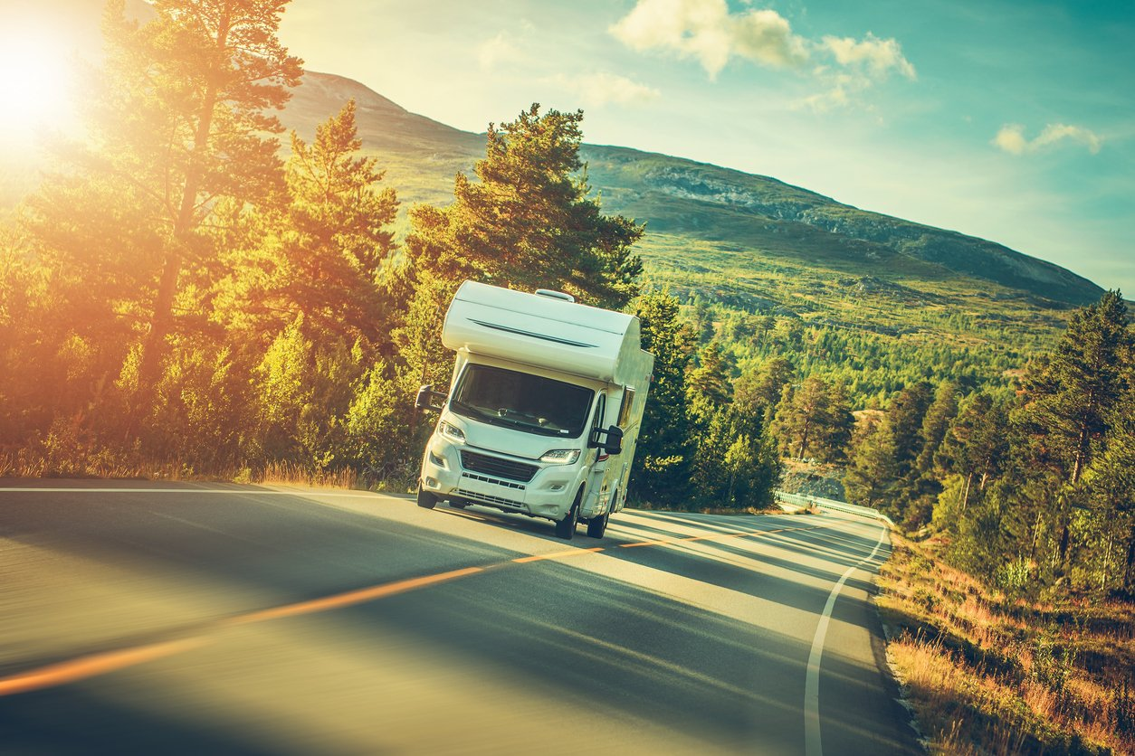 RV Traveling on Road During Sunrise