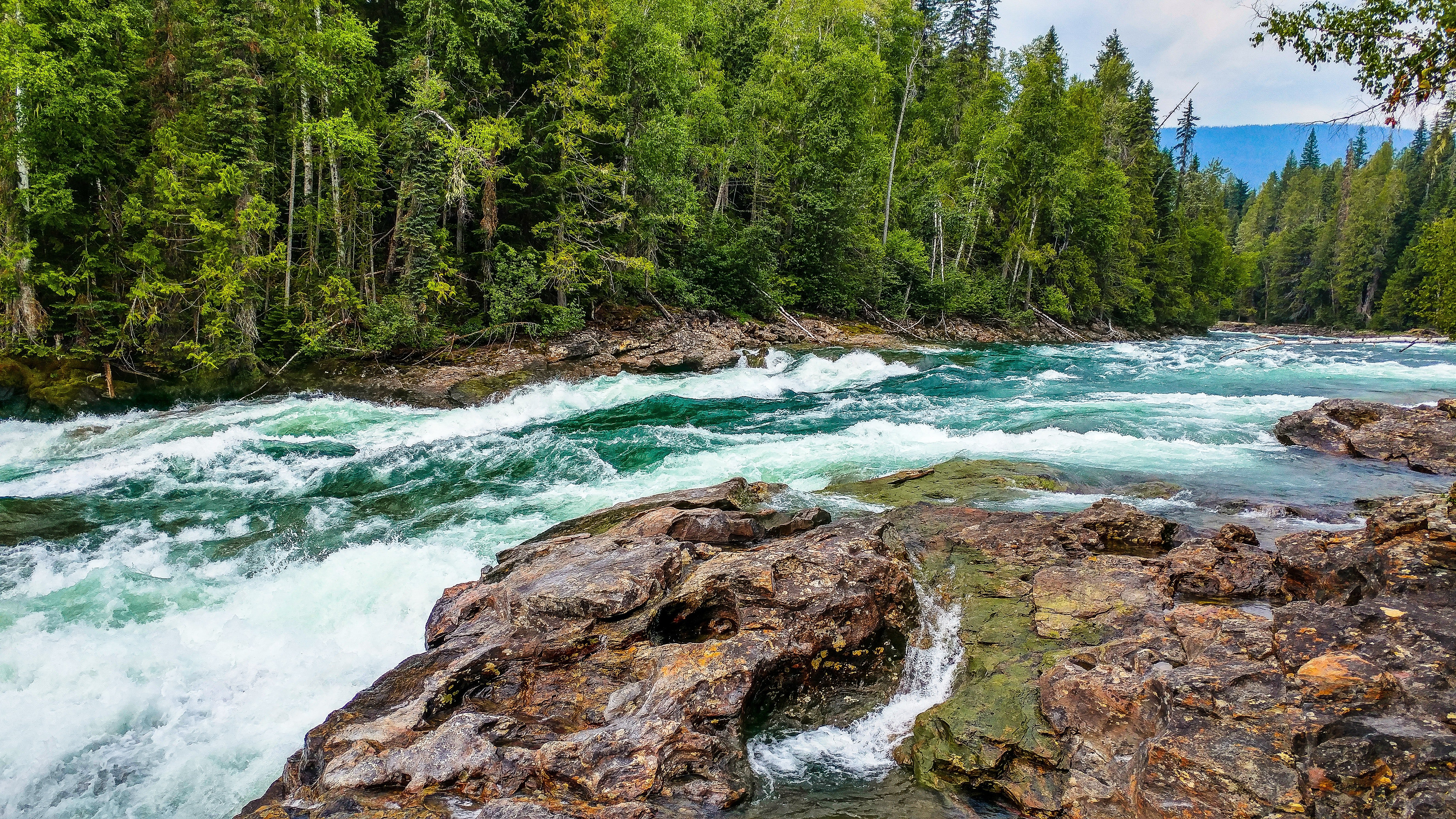 water flowing down river with rocky shore