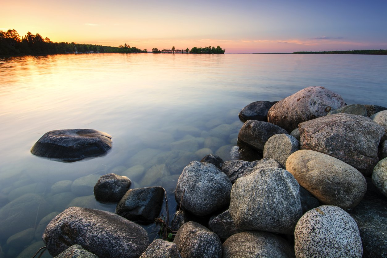 calm lake with boulders at sunset