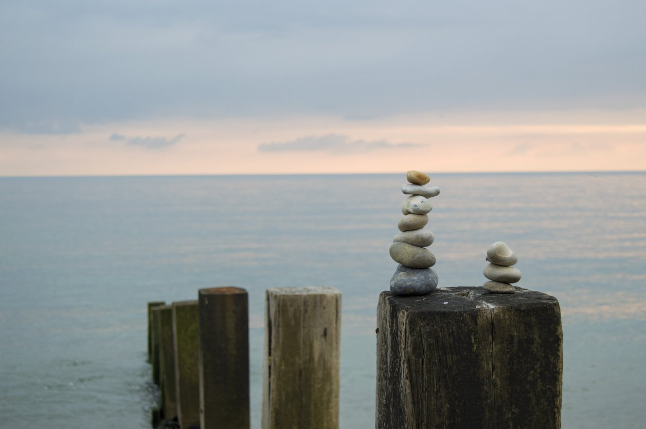 one large stack of stones next to a small stack on post in water