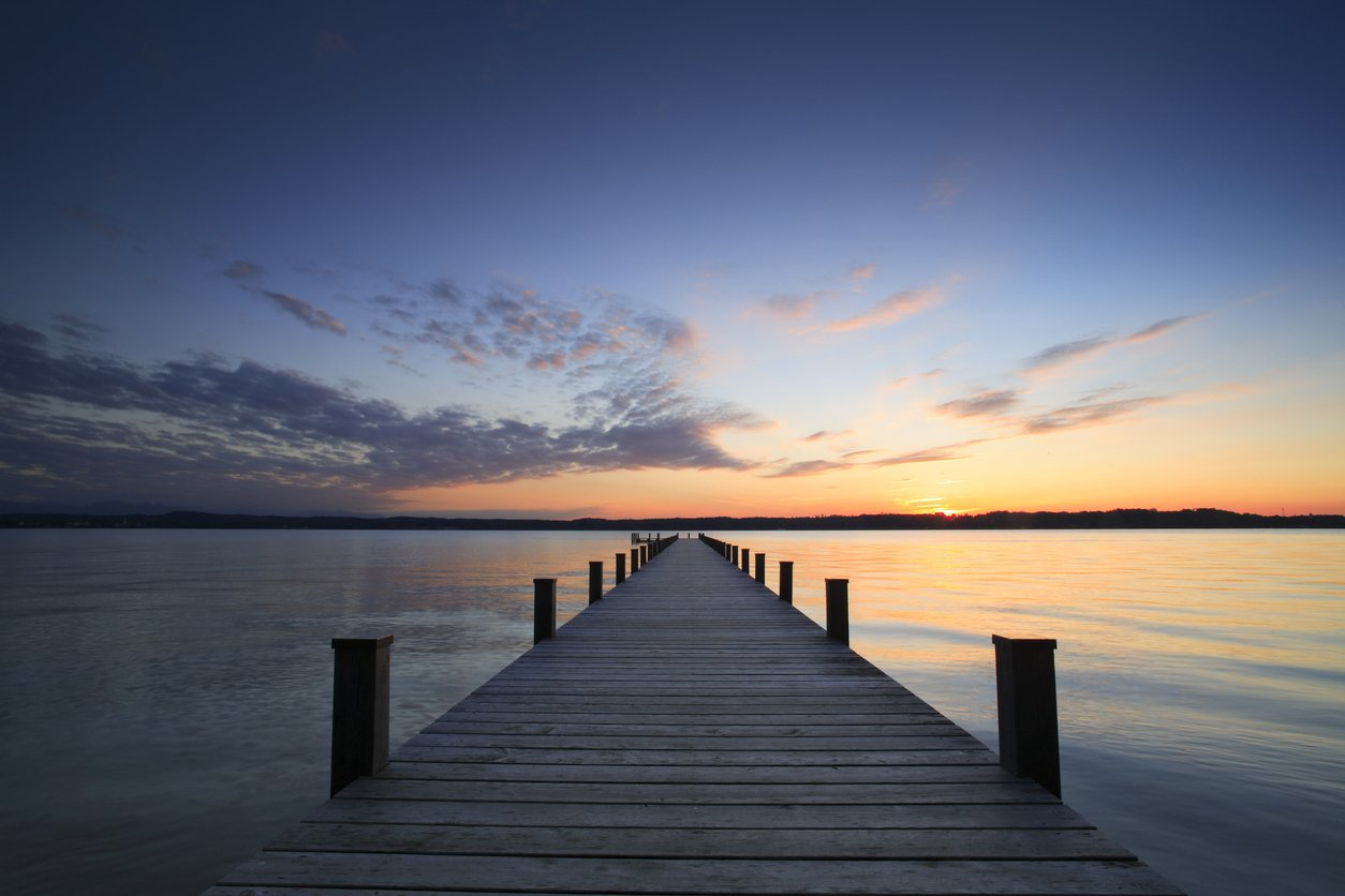 dock on a calm lake at sunset